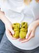closeup woman hands holding baby booties