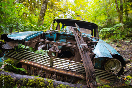 Rusty abandoned car in the forest