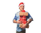 A happy man wearing in a denim shirt and Santa hat holding gifts boxes. - 232862474