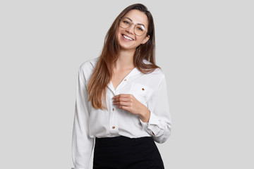 Smiling young lady has toothy smile, pleasant appearance, wears round spectacles, dressed in formal clothes, isolated over white background. Woman office worker rejoices success in her career © sementsova321