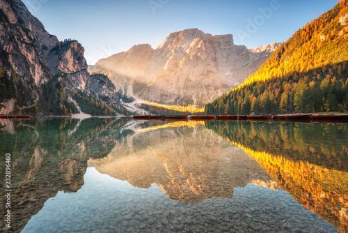 Beautiful Braies lake at sunrise in autumn in Dolomites, Italy. Landscape with mountains, gold sunlight, water with reflection, trees with orange leaves in fall. Travel in italian alps. Dolomiti