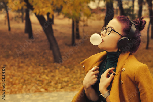 Leinwandbild Motiv Cute young girl listening to music on headphones in autumn park. The girl has eggplant hair. She is wearing glasses and a mustard-colored coat. Woman bubbled up bubble gum