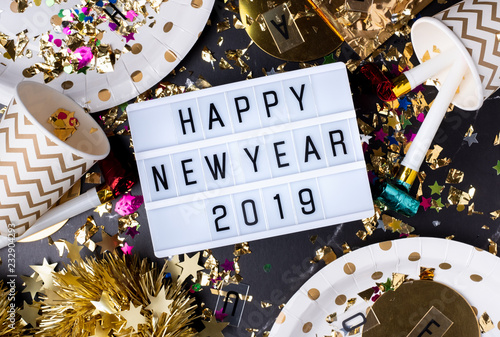 Foto Murales Happy new year 2019 on light box with party cup,party blower,tinsel,confetti.Fun Celebrate holiday party time table top view.