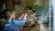 View through a window of a young boy decorating Christmas tree