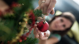 View from above of a woman placing red holiday bauble on Christmas tree - 232920644