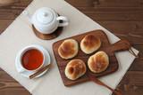 木のまな板にのせた 焼きたて パン 紅茶 ポット テーブル - 232926451