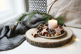 Winter festive still life scene. Burning candle decorated by wooden stars, hazelnuts and pine cones standing near window on wooden cut board. Glittering Christmas lights. Fir branch on wool plaid. - 232927289