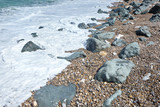 Sea wave with foam and splashes on rocky beach. Pebble stones - 232928476