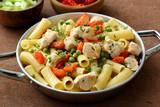 Pasta maccheroni con pollo piselli e verdure in padella di metallo  - 232930025