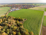 Aerial view of a small piece of forest between fields and meadows behind a village in northern Germany