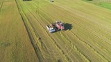 The combine harvester unloads wheat into the truck. - 232936037