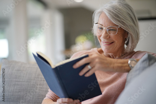 Senior woman reading on couch at home © goodluz