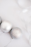 White Christmas background. Glossy silver and glitter decoration balls. Minimalist style. Copyspace for text, overhead - 232947054