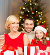 holidays, family and celebration concept - happy mother, father and daughter with gifts at home over christmas tree lights background