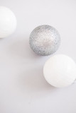 White Christmas background. Glossy silver and glitter decoration balls. Minimalist style. Copyspace for text, overhead - 232947444