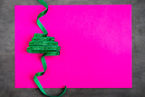 Green glitter ribbon in shape of Christmas tree on vibrant pink colored background. Copyspace for text, overhead - 232947650