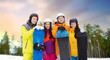 leisure, extreme sport and friendship concept - happy friends in helmets with snowboards outdoors in winter over natural background