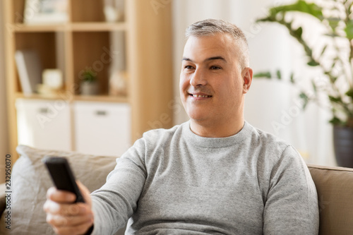 people, television and entertainment concept - man with remote control watching tv at home © Syda Productions