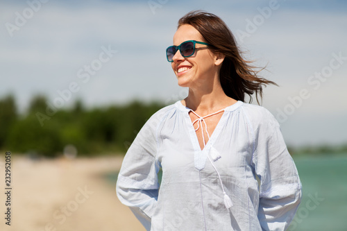 Foto Murales people and leisure concept - happy smiling woman in sunglasses on summer beach