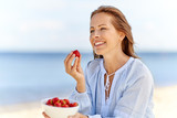 people and leisure concept - happy smiling woman eating strawberries on summer beach