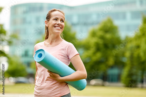 Sticker fitness, sport and healthy lifestyle concept - happy smiling woman with exercise mat at city park