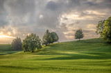 Hilly green pasture meadows in Bavaria at the end of a day - 232954037