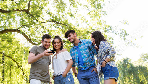 Foto Murales friendship, technology and leisure concept - group of smiling friends with smartphone in summer park