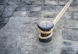 Single bitts with mooring line on a cobbled quay of the Seine River in Paris - 232956220