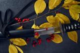 Autumn still life. Samurai sword, katana on a dark background in yellow leaves with red rowan.