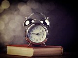 metal alarm clock and open book. Photo in old color image style. - 232959028