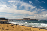 Dramatic seascape with golden beach and waves on a cloudy day on a volcanic island. - 232961056