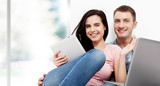 Happy young couple sitting on the floor with a laptop looking fo - 232961850