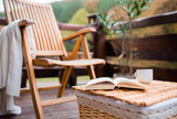 A wooden chair and a book on a basket on a terrace on a sunny day in autumn. - 232965823