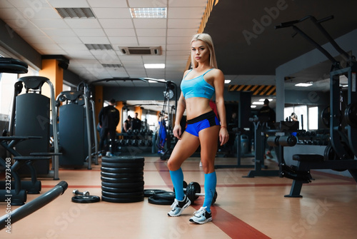Sticker Sexy girl in blue suit, golf in the gym
