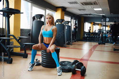 Sticker Sexy girl in blue suit, long socks in the gym sitting on the equipment