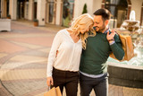 Portrait of happy loving couple with shopping bags - 232977649