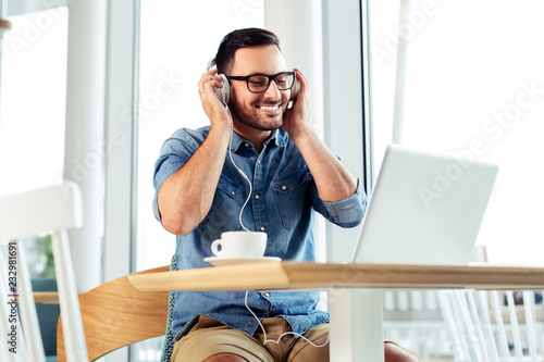 Handsome student studying in a cafe with his headphones on. - 232981691