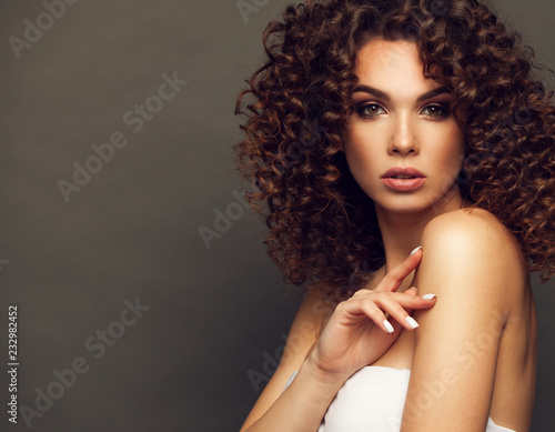 Leinwandbild Motiv Fashion studio portrait of beautiful smiling woman with afro curls hairstyle. Fashion and beauty.