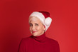 Smiling mature woman in red santa claus hat.