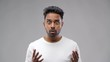 emotion, expression and people concept - shocked indian man over grey background