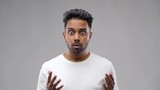 emotion, expression and people concept - shocked indian man over grey background - 232988444