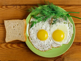 Fried eggs of 2 eggs with a piece of bread, dill and fork on the table. - 232989045