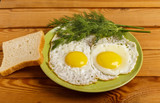 Fried eggs of 2 eggs with a piece of bread, dill and fork on the table. - 232989058