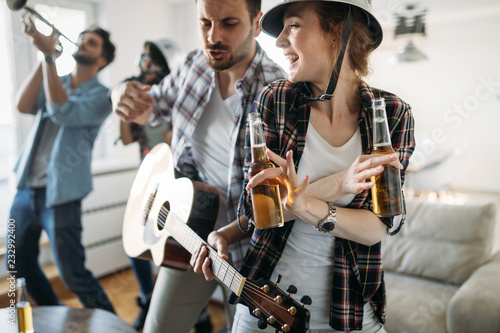 Foto Murales Cheerful friends having party together and playing instruments