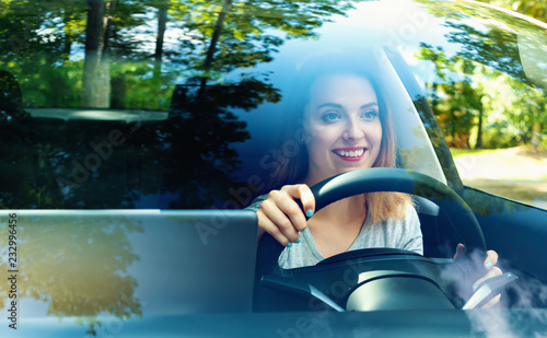 Wall mural Young woman driving a new luxury car