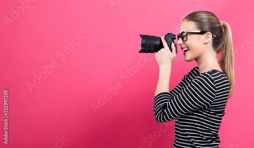 Leinwandbild Motiv Young woman with a professional digital SLR camera on a pink background