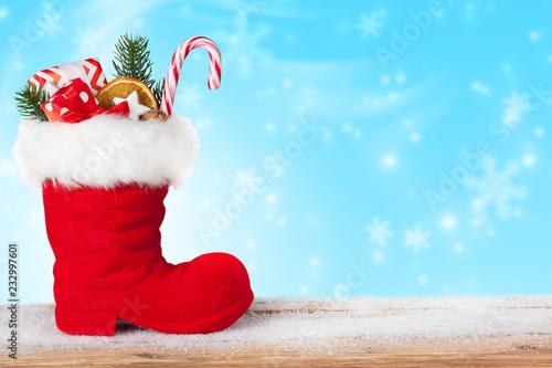 Leinwanddruck Bild Weihnachtsmann Stiefel gefüllt mit Süßigkeiten und Geschenken mit Schnee Hintergrund