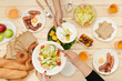 Enjoying dinner with friends.  Top view of group of people having dinner together while sitting at wooden table - 232998221