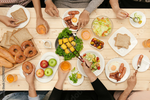 Wall mural Enjoying dinner with friends.  Top view of group of people having dinner together while sitting at wooden table