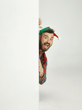 The happy smiling friendly man dressed like a funny gnome or elf posing on an isolated gray studio background. The winter, holiday, christmas concept - 232998881